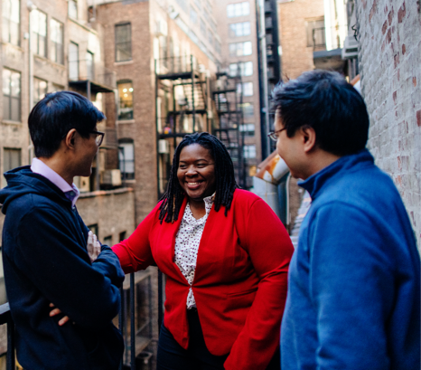 Photo of three colleagues standing outside enjoying conversation