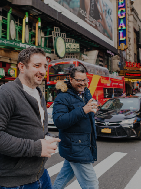 Photo of two colleagues crossing the street while drinking coffee