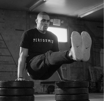 Man in Performix tee raised on stacks of barbell weights doing leg extension exercise