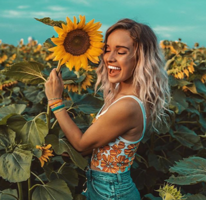 Happy blonde woman holding sunflower to her face eyes closed in sunflower field wearing Pura Vida bracelets