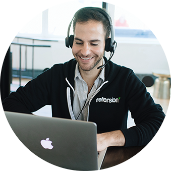Smiling man wearing Refersion logo jacket using apple macbook answering call on headset